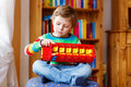 Little blond kid boy playing with wooden toy bus, indoors Royalty Free Stock Photo