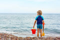 Little blond kid boy standing on lonely ocean beach Royalty Free Stock Photo