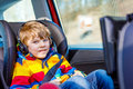 Little blond kid boy watching tv or dvd with headphones during long car drive Royalty Free Stock Photo