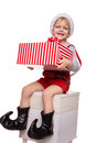 Little blond kid in red costume of dwarf holding big gift box with ribbon. Christmas concept Royalty Free Stock Photo