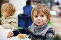 Little blond toddler boy eating ice cream iin shopping mall indoor Royalty Free Stock Photo