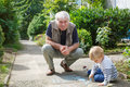 Little blond toddler boy and happy grandfather painting with cha Royalty Free Stock Photo