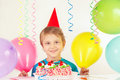 Little blonde boy in festive cap with birthday cake and balloons Royalty Free Stock Photo