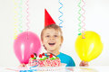 Little blonde boy in holiday cap with birthday cake and balloons Royalty Free Stock Photo