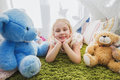 Little blonde child girl playing at home in her room with teddy bears Royalty Free Stock Photo