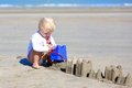 Little blonde girl building sand castles on the beach Royalty Free Stock Photo