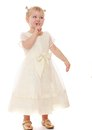 Little blonde girl in a long air delicate bright dress and golden sandals on his feet put to the lips of the index finger gesture Royalty Free Stock Photography