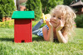 Little blonde girl lying on the grass with house toy Stock Photo