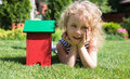Little blonde girl lying on grass the with house toy Stock Images