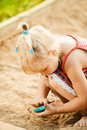 Little blonde girl playing in sandpit pretty at summer green park Royalty Free Stock Image