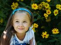 Little blonde girl sits among yellow flowers Royalty Free Stock Images