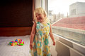 little blonde girl stands by window side-view Royalty Free Stock Photo