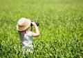 Little blonde girl in straw hat looking through binoculars