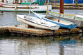 Little boats secured on dock when not in use the two small sailboats and the rowboat are to the top of the floating in the harbor Royalty Free Stock Photography