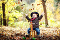 Little boy in the autumn forest on wooden rocking horse Stock Photo