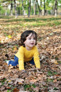Little boy in autumn park photo of cute having fun pretty child sitting on dry old orange foliage woods small kid playing with Royalty Free Stock Image