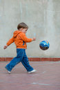 Little boy in the backyard with a ball playing Stock Photography