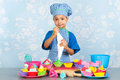 Little boy baking cupcakes is colorful with vintage wall paper in background Royalty Free Stock Images