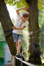 Little boy balancing on a tightrope the background of trees in the park Stock Photos