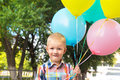 Little boy with balloons beautiful happy cute joyful smiling blond child bunch of in hands close up outdoor portrait birtday fun Stock Photos