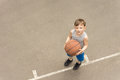 Little boy with a basketball looking puzzled Royalty Free Stock Photo