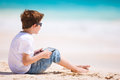 Little boy beach playing tablet device Stock Images