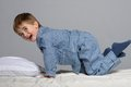 Little boy in bed wearing blue pyjamas Stock Images