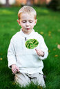Little boy with big lollipop on a green lawn Royalty Free Stock Image