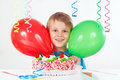 Little boy with a birthday cake and balloons on white background Royalty Free Stock Photo