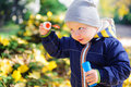 Little boy blowing soap bubbles in autumn park Royalty Free Stock Photos