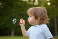Little boy blowing soap bubbles in park Royalty Free Stock Photography