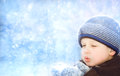 Little boy blows snow with mittens on bokeh background of snowflakes Stock Photo