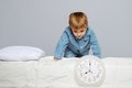 Little boy in blue pyjamas with clock Royalty Free Stock Photos