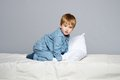 Little boy in blue pyjamas wearing bed Royalty Free Stock Image