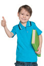 Little boy with book holds his thumb up a on the white background Royalty Free Stock Photo