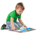 Little boy with a book sitting on the floor enthusiastic isolated white Stock Photo