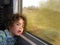 Little boy bored on the train journey adorable putting his head down to window Stock Image