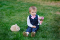 Little boy with a bouquet of flowers and a rabbit sitting on the grass Royalty Free Stock Photography