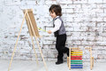 Little boy in bow tie stands next to easel and colorful abacus studio with white brick wall Royalty Free Stock Image