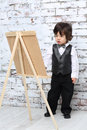 Little boy in bow tie stands next to easel in studio with white brick wall Stock Image