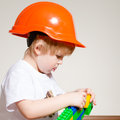 Little boy in builder helmet playing with constructor orange studio over white background Royalty Free Stock Images