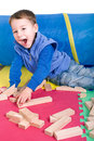 Little boy building with blocks small laughing builds on colorful playmat Stock Photography