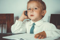 Little boy in a business suit proudly talking on the phone while sitting at the round table Stock Image