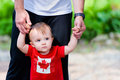 Little boy in canada shirt toddler lost thought wearing a flag walking assisted by his father Stock Photography