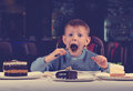 Little boy cannot believe his luck he sits dining table holding fork gawping array different cakes spread out front him wonderment Royalty Free Stock Images