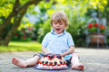 Little boy celebrating his birthday in home s garden with big ca adorable cake Stock Image