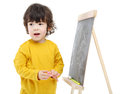 Little boy with chalk stands near chalkboard isolated on white background Royalty Free Stock Images