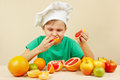Little boy in chefs hat eat fresh acidic grapefruit at table with fruits the Stock Photography