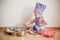 Little boy in a chief hat and aprons cooking Royalty Free Stock Photo