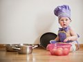 Little boy in a chief hat and aprons sitting on a floor Royalty Free Stock Photo